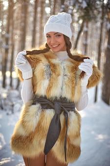 Futrzana kamizelka na pięknej młodej kobiecie rasy białej w zimowym słonecznym lesie