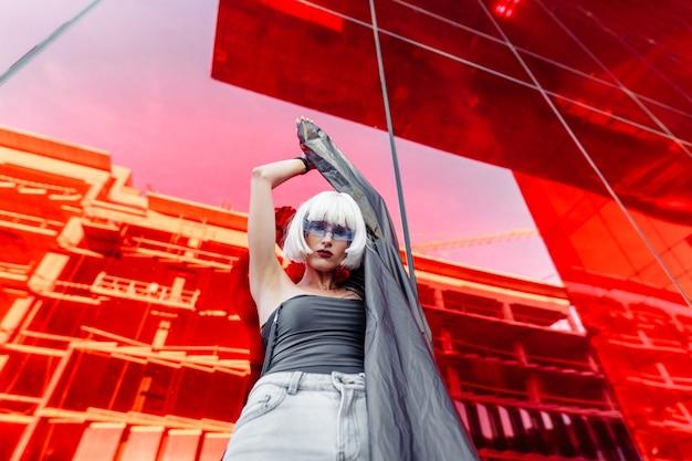 Futurystyczny styl. kobieta w okularach, w pobliżu czerwonego futurystycznego budynku.
