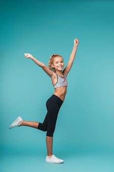 Fyll długość szczęśliwa mała dziewczynka ubrana w odzież sportową stojącą na białym tle nad niebieską ścianą, pozowanie
