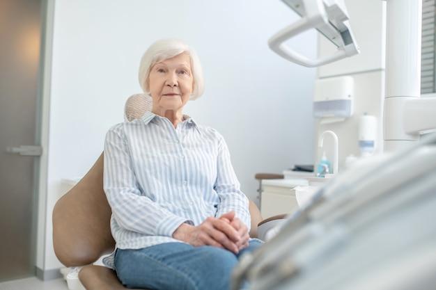 Gabinet dentystyczny. starsza kobieta siedzi w gabinecie dentystycznym i czeka na lekarza