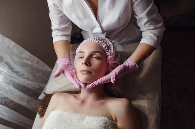 Gabinet kosmetyczny, kosmetyczka wykonuje masaż twarzy młodej pięknej kobiecie