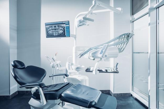 Gabinet stomatologiczny z komputerem na fotelu dentystycznym i narzędziami dentystycznymi