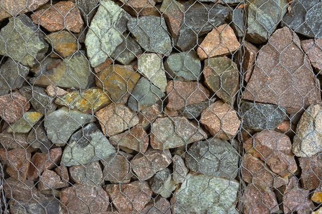 Gabion, tekstura, tło. ściana wykonana z naturalnych skał i metalowych płotów. architektura krajobrazu. ogrodzenie i tarasy