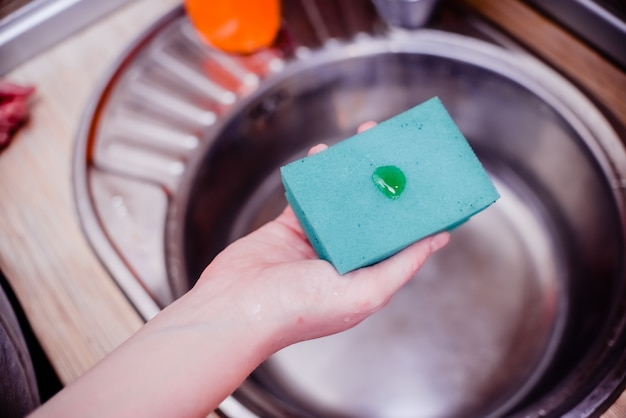 Gąbka do naczyń z mydłem do mycia naczyń.