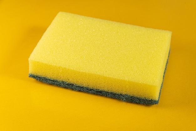 Gąbka kuchenna na żółtym tle