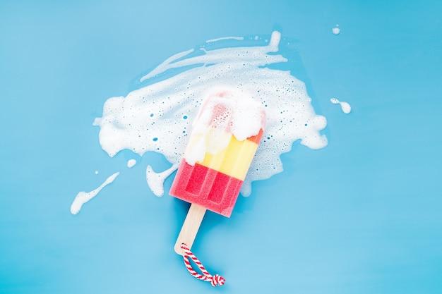 Gąbka w postaci lodów na tle piany mydlanej. koncepcja mycia naczyń. leżał płasko, widok z góry.