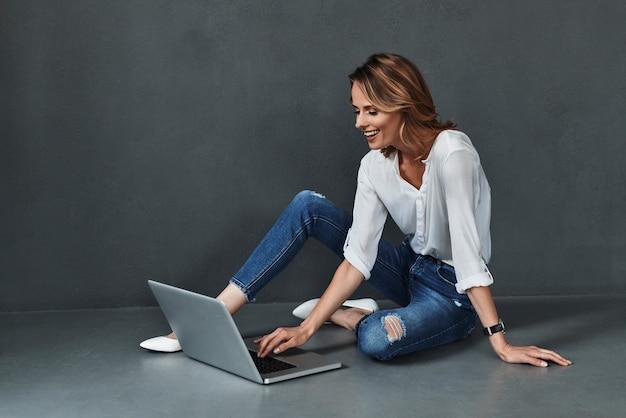 Gadać na czacie online, rozmawiać online. atrakcyjna młoda kobieta w stroju casual, korzystająca z komputera i uśmiechająca się siedząc na podłodze na szarym tle