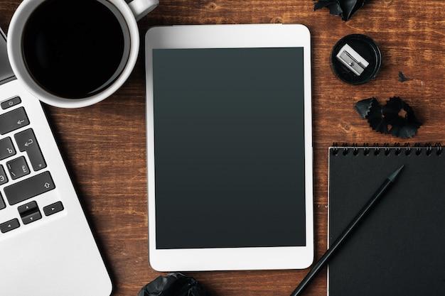 Gadżety elektroniczne i materiały biurowe na drewnianym stole