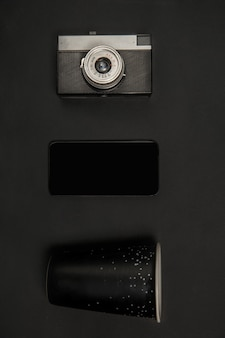 Gadżety i okulary. monochromatyczna stylowa i modna kompozycja w czarnym kolorze na ścianie studia. widok z góry, układ płaski.