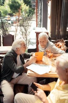 Gadżety i whisky. widok z góry na emerytowanych siwowłosych mężczyzn korzystających z gadżetów i pijących whisky
