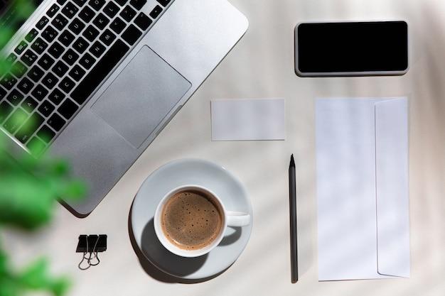 Gadżety, kawa, narzędzia pracy na białym stole w pomieszczeniu.