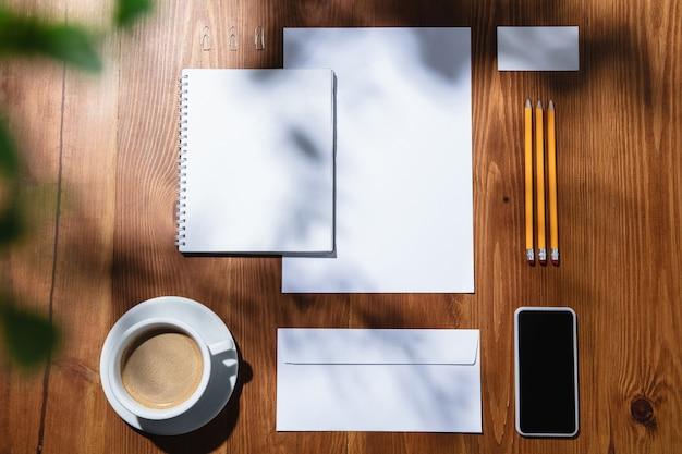 Gadżety, kawa, narzędzia pracy na drewnianym stole w pomieszczeniu. kreatywne, przytulne miejsce pracy w domowym biurze, inspirująca makieta z cieniami roślin na powierzchni. koncepcja zdalnego biura, freelance, atmosfera.