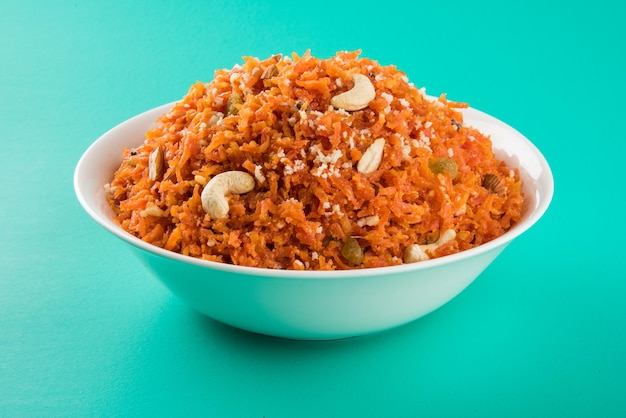 Gajar halwa to słodki pudding deserowy na bazie marchwi z indii. przyozdobiony orzechami nerkowca, migdałami i podawany w misce na kolorowym drewnianym tle