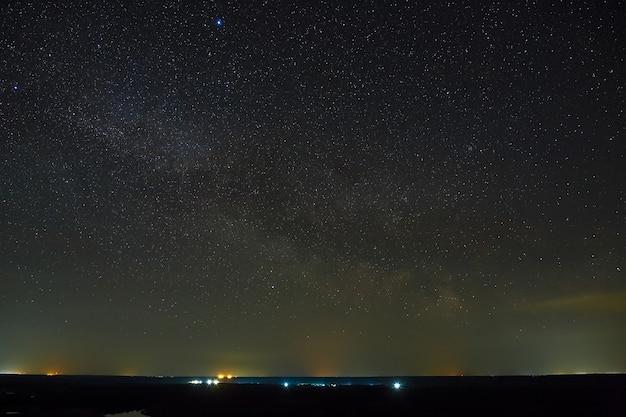 Galaktyka droga mleczna na nocnym niebie z gwiazdami. przestrzeń nad powierzchnią ziemi. długa ekspozycja.