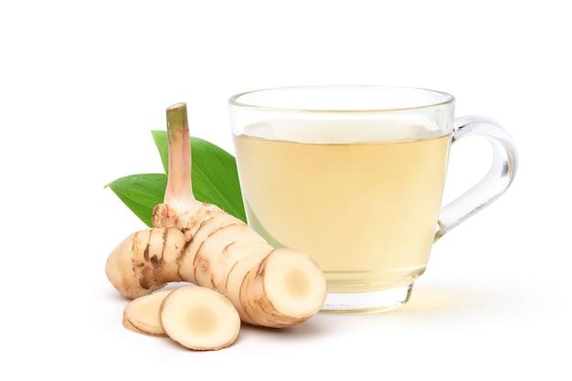 Galangal napój ziołowy z plastrami świeżych kłączy na białym tle.