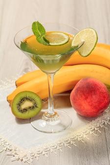 Galaretka kiwi z kawałkami limonki w liściach mięty zwieńczone szklanką, nektarynka, kiwi i banan na białej serwetce
