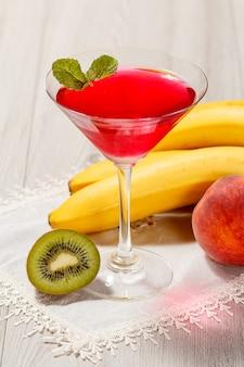 Galaretka wiśniowa w szklance zwieńczone listkami mięty, nektarynka, kiwi i banan na białej serwetce