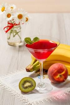 Galaretka wiśniowa w szklanych zwieńczonych liśćmi mięty, nektarynka, kiwi, banan i bukiet rumianków na drewnianym tle
