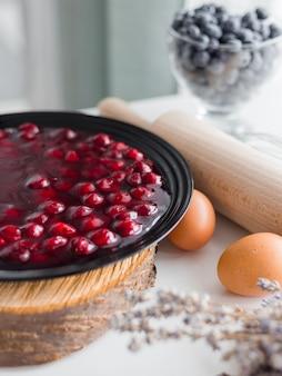 Galaretka z czerwonych owoców w misce, domowa konfitura wiśniowa w czarnym talerzu, w stylu rustykalnym