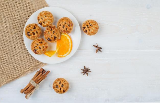 Galaretki nadziewane ciastka i pomarańcza w talerzu z cynamonem i podkładką