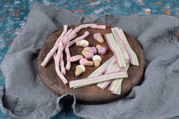Galaretki o mieszanym kształcie i kolorze na drewnianym talerzu.