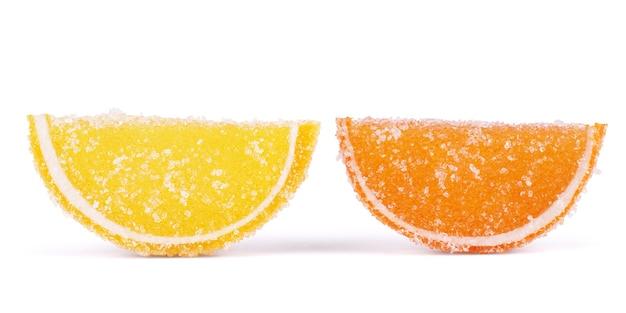 Galaretki owocowe. cytrusowe cukierki galaretkowe w formie zrazików na białym tle