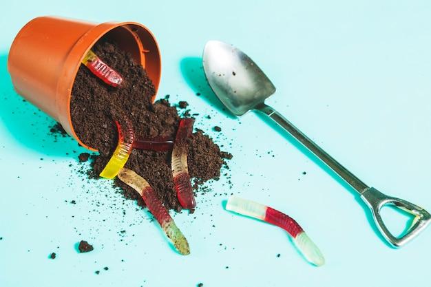 Galaretowate robaki w przewracającym się garnku z ziemią w pobliżu łopaty