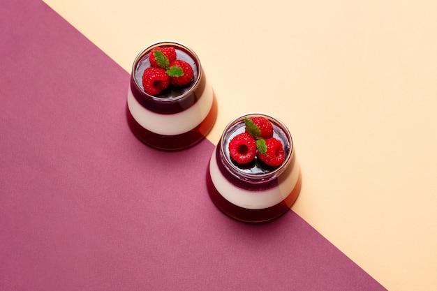 Galaretowe jagody z malinami w szklanej filiżance na kolorowym tle