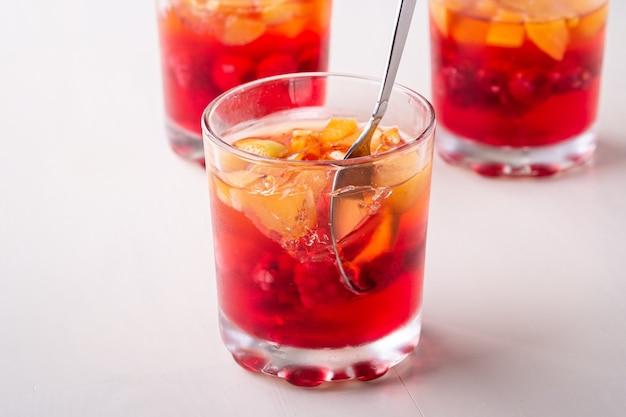 Galaretowy deser z owoc morelową malinką w trzy pije szkłach z pojedynczą łyżką, lata pojęcie, biel ściana odizolowywająca