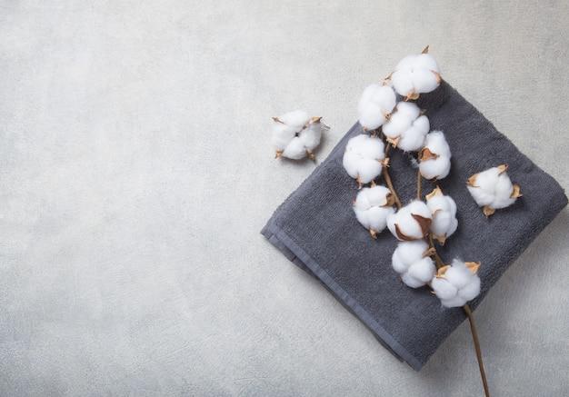 Gałąź bawełniani i baige szarzy ręczniki na betonowym tle.