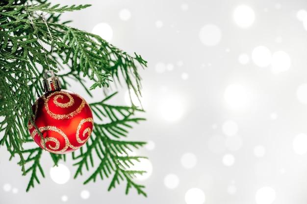 Gałąź choinki z piłką na tle bokeh. koncepcja nowego roku, kartka świąteczna.