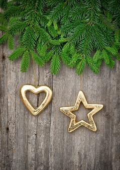 Gałąź choinki ze złotą dekoracją na drewnianym tle. stonowany obraz w stylu vintage