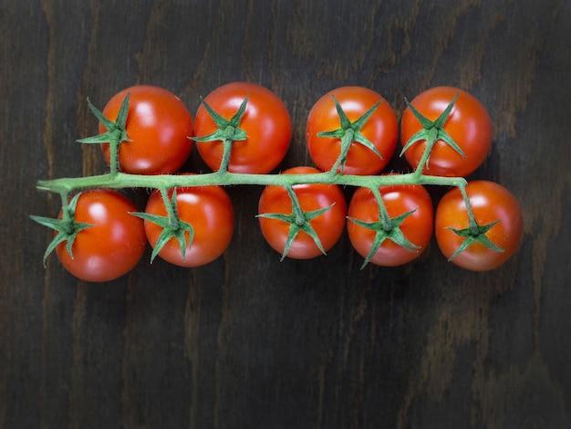 Gałąź czerwonych dojrzałych świeżych pomidorów koktajlowych na drewnianej desce