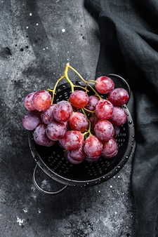 Gałąź czerwonych soczystych winogron w durszlaku