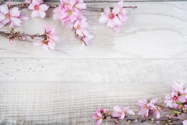 Gałąź drzewa migdałowego z kwiatami na tle drewnianych. rama kwiatowa.
