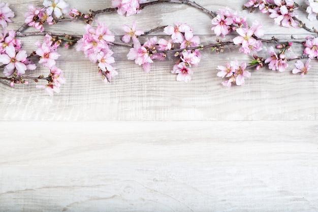 Gałąź drzewa migdałowego z kwiatami na tle drewnianych.