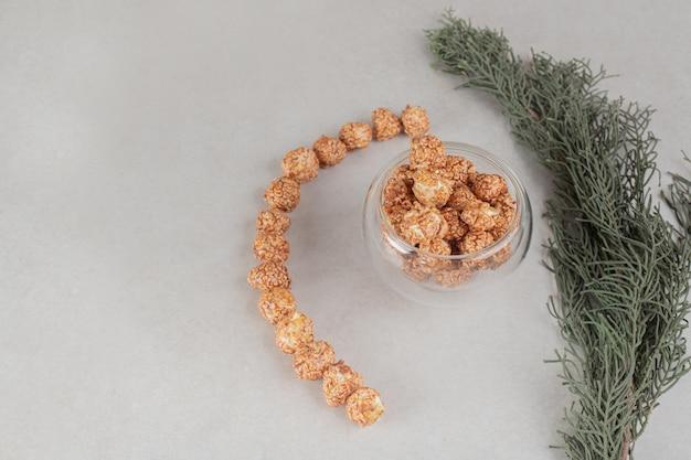 Gałąź drzewa obok dekoracyjnie ułożonej masy popcornowych cukierków na marmurowym stole.