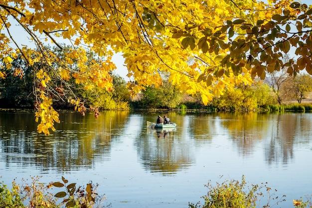 Gałąź klonu ze złotymi jesiennymi liśćmi nad rzeką, na której rybacy łowią z łodzi