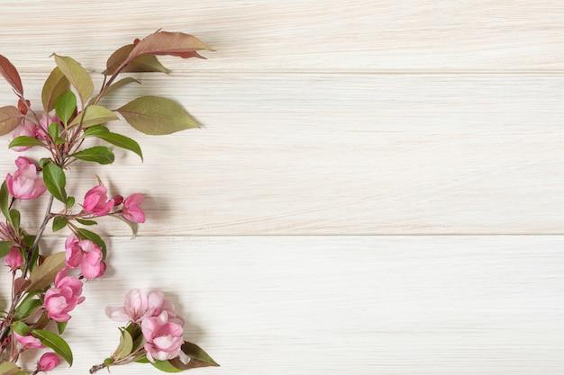 Gałąź kwitnie jabłoń na drewnianym stole. leżał płasko