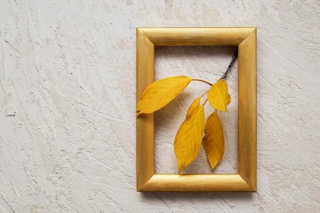 Gałąź pomarańczowych liści w złotej ramce. koncepcja jesień.