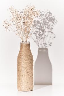 Gałąź roślin w ręcznie robionym wazonie z cieniami. nowoczesna koncepcja wystroju wnętrz. minimalistyczny styl