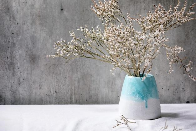 Gałąź suchych białych kwiatów w białym ceramicznym wazonie na białym lnianym obrusie z szarą ścianą z tyłu
