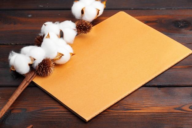 Gałąź z bawełną kwitnie na drewnianym tle