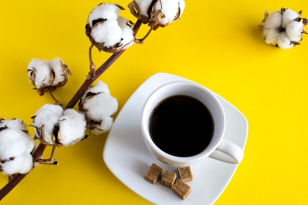 Gałąź z bawełny i kawy na stole żółty. widok z góry.