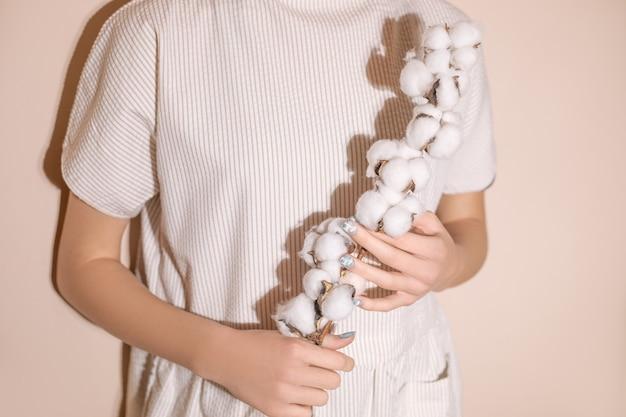 Gałązka bawełny z kuleczkami w kobiecych dłoniach, sukienka wykonana z naturalnych materiałów.