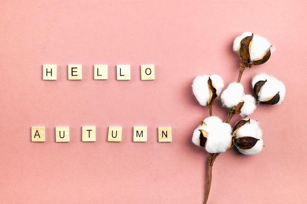 Gałązka dojrzałej bawełny i napis drewnianymi literami witaj jesień na różowym tle mieszkanie leżące widok z góry koncepcja sezonowa