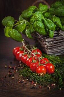 Gałązka dojrzałych pomidorów między zielonymi ziołami