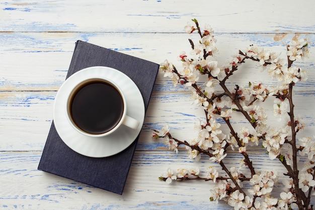 Gałązka wiśni z kwiatami i biała filiżanka z czarną kawą i książką na białym drewnianym tle.
