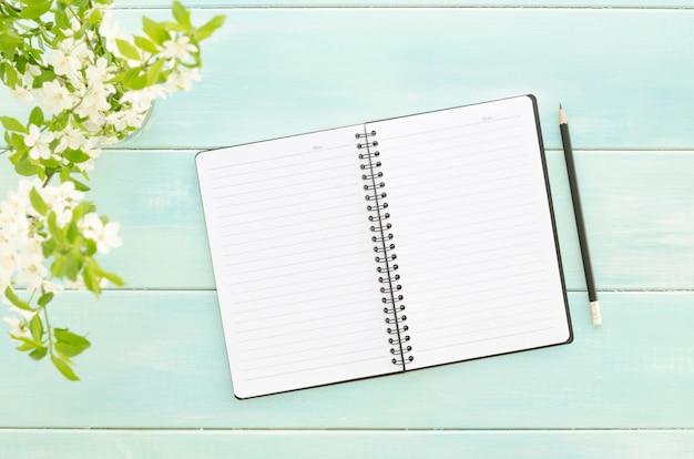 Gałązka z białymi kwiatami na tle mięty z notatnikiem i ołówkiem. koncepcja wiosny. zdjęcia znad głowy