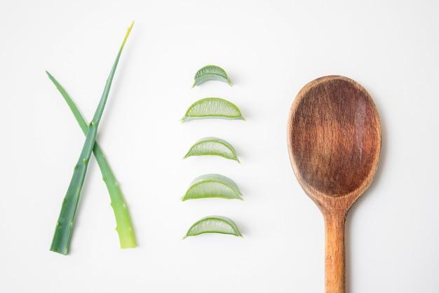 Gałązki aloesu i plastry roślin na białym tle drewnianą łyżką.
